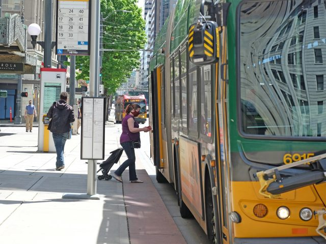 Woman wearing face mask boarding a bus in downtown Seattle