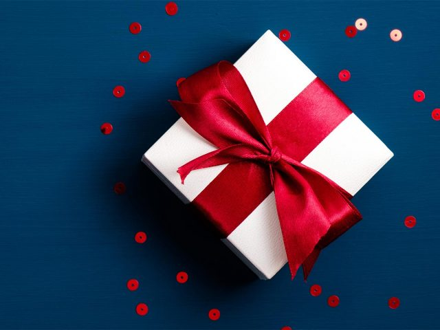 White gift box wrapped in a red ribbon on blue background surrounded by scattered sequins