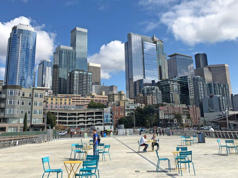Pier 62 in downtown Seattle: People sitting at bistro tables and chairs on a sunny day, cityscape in background. Blue sky with clouds.