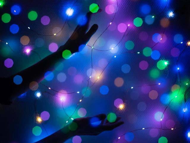 Holiday lights, hand reaching out, blue background with magenta, green, blue and orange lights