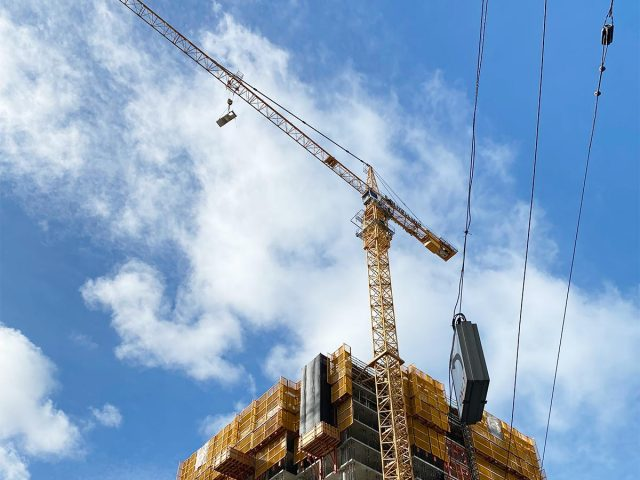 Construction crane against a blue sky with white clouds
